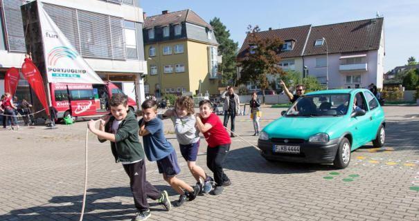 Ivica, Gökay, Dzenis und Haydar legen sich mächtig ins Zeug, um das Auto mit ihren Lehrern über den Schulhof zu ziehen.